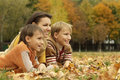 Portrait of a beautiful mother and her children are in the autumn park Stock Photo