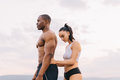 Portrait of beautiful muscular mixed race couple with perfect bodies in sportswear softly embracing on mountains landscape Royalty Free Stock Photography