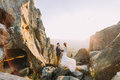 Portrait of beautiful newlywed couple in sunset lights on majestic mountain landscape with big rocks as backround Royalty Free Stock Photo
