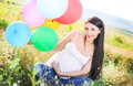 Portrait of a beautiful pregnant woman with bright colorful balloons in nature Royalty Free Stock Photo