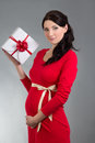 Portrait of beautiful pregnant woman in red dress with gift box young over grey background Stock Photos