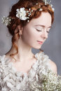 Portrait of beautiful red-haired bride. She has a perfect pale skin and delicate blush.