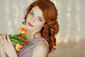Portrait of a beautiful red-haired girl with blue eyes holding a Royalty Free Stock Photo