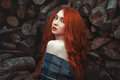 Portrait of beautiful redhaired girl i in a warm sweater llogs background Stock Photo