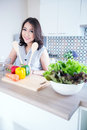 Portrait of beautiful relaxed young woman standing at the kitchen counter Royalty Free Stock Image