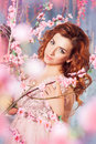 Portrait of beautiful romantic girl among oriental cherry blossom tree brunches in spring garden. Royalty Free Stock Photo