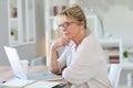 Portrait of beautiful senior woman on laptop working computer Royalty Free Stock Image