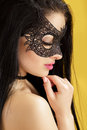 Portrait of beautiful sensual woman in black lace mask on yellow background. sexy girl in venetian mask Royalty Free Stock Photo