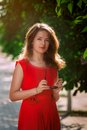 Portrait of a beautiful sexy fashion girl in a red dress on the nature of the park Stock Photography