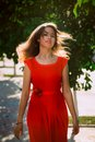 Portrait of a beautiful sexy fashion girl in a red dress on the nature of the park Royalty Free Stock Image