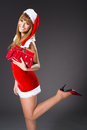 Portrait of beautiful sexy girl wearing santa claus clothes on gray background Stock Photo