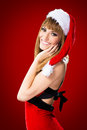 Portrait of beautiful sexy girl wearing santa claus clothes on red background Stock Photography