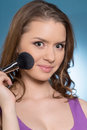 Portrait of beautiful sexy girls with makeup brush young woman on blue background Royalty Free Stock Photo