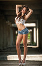 Portrait of a beautiful sexy woman with denim shorts and white cropped t shirt in urban background attractive brunette posing Royalty Free Stock Images