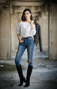 Portrait of beautiful sexy young woman with modern outfit, leather jacket, jeans, white blouse and black boots Royalty Free Stock Photo