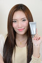 Portrait of beautiful smiling asian woman is holding cosmetic c healthy container Royalty Free Stock Images