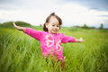 Portrait of beautiful smiling carefree girl playing outdoors in field Stock Image
