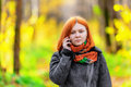 Portrait of beautiful smiling red haired woman talking by mobile phone shallow dof Royalty Free Stock Photography