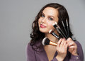 Portrait beautiful smiling woman makeup brushes near her face Royalty Free Stock Photo