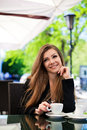 Portrait of beautiful smiling woman sitting in a cafe with laptop outdoor brunette long hair an for cup coffee Royalty Free Stock Images