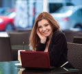 Portrait of beautiful smiling woman sitting in a cafe with laptop outdoor brunette long hair an for cup coffee Stock Photo