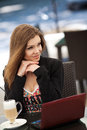 Portrait of beautiful smiling woman sitting in a cafe with laptop outdoor brunette long hair an for cup coffee Royalty Free Stock Photo