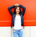 Portrait beautiful smiling young brunette woman wearing a rock black leather jacket and jeans posing in city Royalty Free Stock Photo