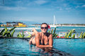 Portrait of beautiful tanned woman in black swimwear relaxing in swimming pool spa. Hot summer day and bright sunny