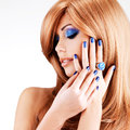 Portrait of a beautiful woman with blue nails blue makeup and red hairs on white background Royalty Free Stock Image