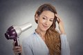 Portrait beautiful woman with a hairdryer headshot on grey wall background Stock Photos
