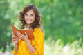 Portrait of beautiful woman holding book young attractive dark haired curly wearing orange sweater and at summer green park Stock Photos