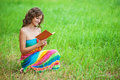 Portrait of beautiful woman holding book young attractive dark haired curly wearing orange sweater and at summer green park Royalty Free Stock Photos