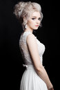 Portrait of beautiful woman in lace dress posing at dark studio. Blonde bride with stylish haircut, earrings with diamonds and acc Royalty Free Stock Photo