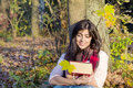 Portrait of a beautiful woman leaning on a tree with book in the autumn park Royalty Free Stock Photo