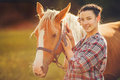 Portrait beautiful woman next horse in warm summer sunny day cropped view of young female rider smiling and embracing her Stock Photo