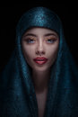 Portrait of a beautiful woman in paranja with arabian makeup on dark background Stock Photos