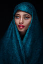 Portrait of a beautiful woman in paranja with arabian makeup isolated on dark background Royalty Free Stock Photo