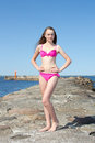 Portrait of beautiful woman in pink bikini posing on rocky beach young Royalty Free Stock Images