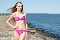 Portrait of beautiful woman in pink bikini standing on rocky bea young beach Stock Photos