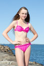Portrait of beautiful woman in pink on rocky beach young Stock Image