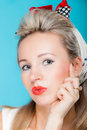 Portrait beautiful woman pinup girl retro style blowing a kiss - flirty on blue Royalty Free Stock Photo