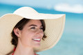 Portrait of a beautiful woman in a sunhat closeup the face brunette wide brimmed floppy straw posing at the sea Stock Photo