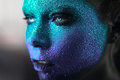 Portrait of beautiful woman with violet and blue sparkles on her