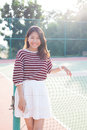 Portrait of beautiful young asian woman wearing white clothes skirt in tennis course with happy face Royalty Free Stock Photo