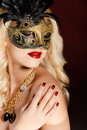 Portrait of a beautiful young blond woman with theatrical mask on his face on a dark background Stock Photography