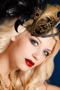 Portrait of a beautiful young blond woman with theatrical mask on his face on a dark background Royalty Free Stock Photography