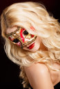 Portrait of a beautiful young blond woman with theatrical mask on his face on a dark background close up in venetian carnival Royalty Free Stock Photo