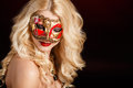 Portrait of a beautiful young blond woman with theatrical mask on his face on a dark background close up in venetian carnival Stock Photo