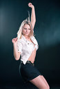 Portrait of a beautiful young blonde dancing girl in white jacket and black skirt on dark background Royalty Free Stock Image