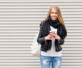 Portrait of a beautiful young blonde girl with long hair posing on a street with coffee and a backpack. Look at the camera. Outdoo Royalty Free Stock Photo